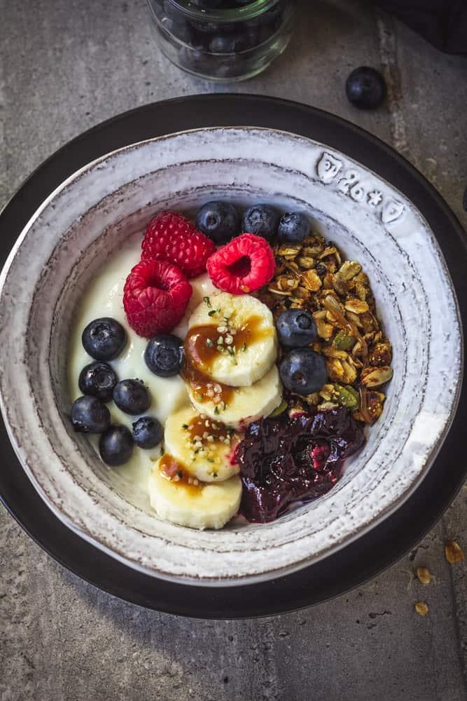 Bowl of crunchy granola, plant-based yogurt and fresh fruit.