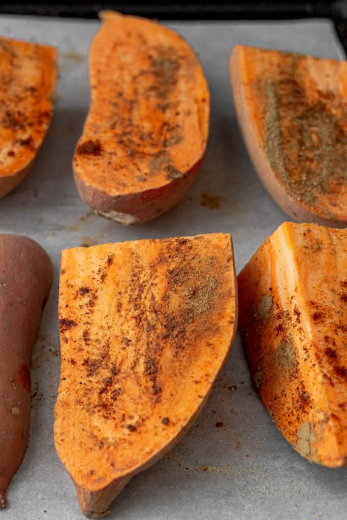Baking tray of raw sliced sweet potatoes.