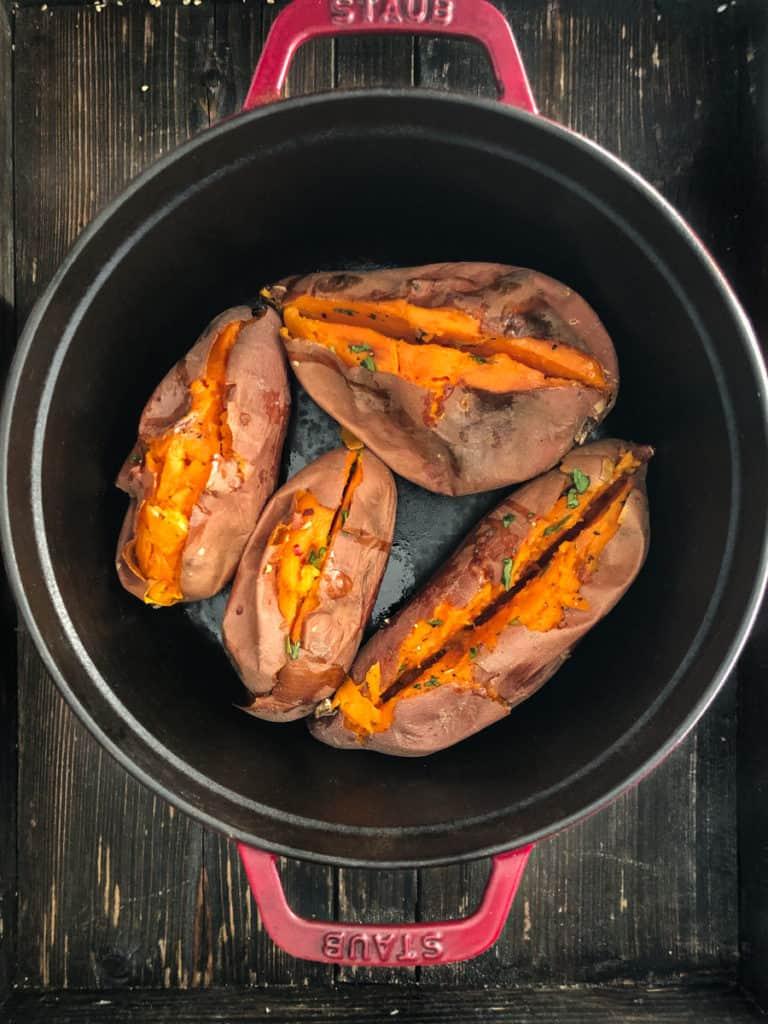Dutch oven full of baked sweet potatoes slit open.