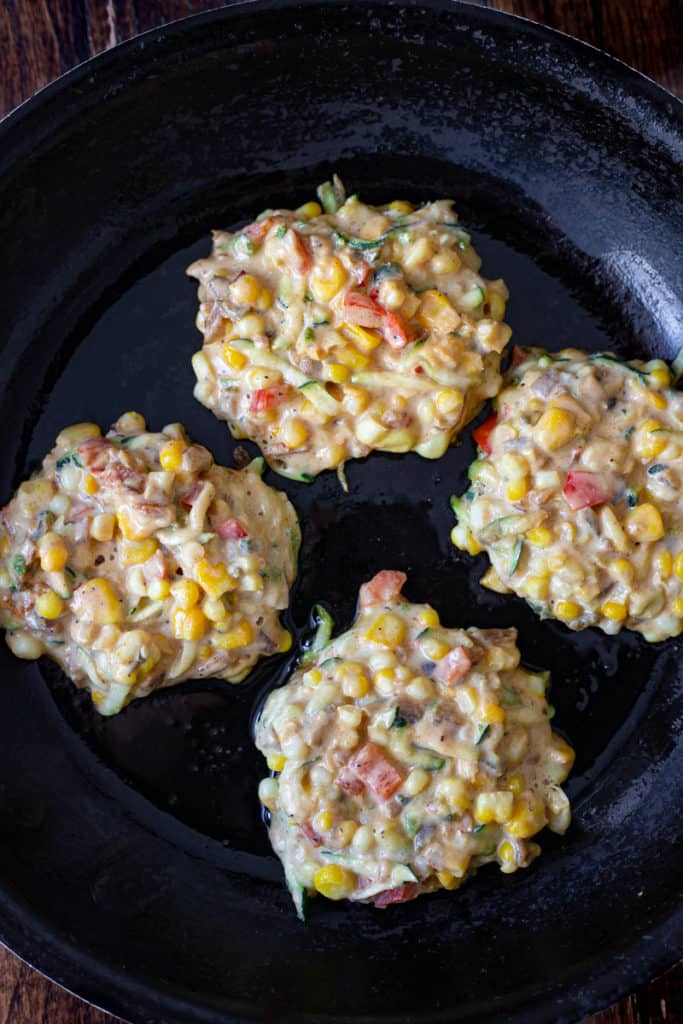Vegan corn fritters frying in a skillet.