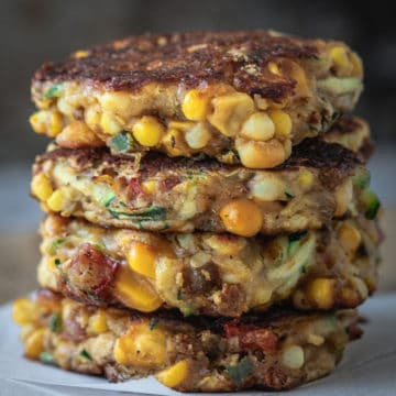 Stack of vegan corn fritters on a serving board.