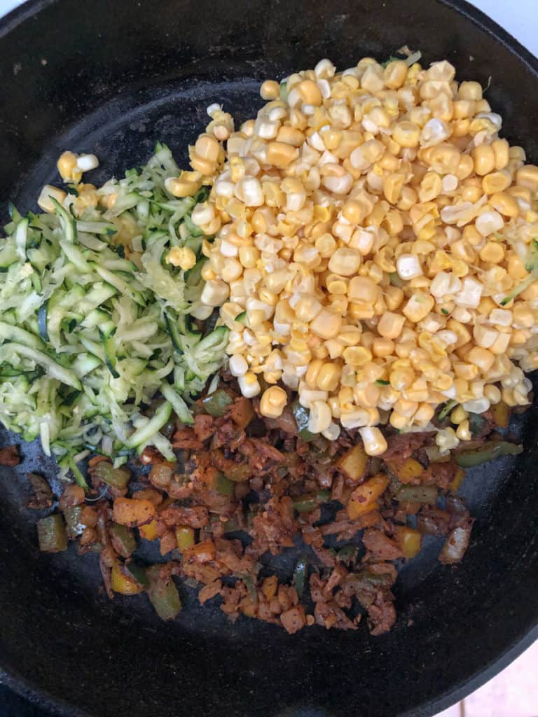 Grated zucchini, fresh corn, and spiced onions in a skillet.