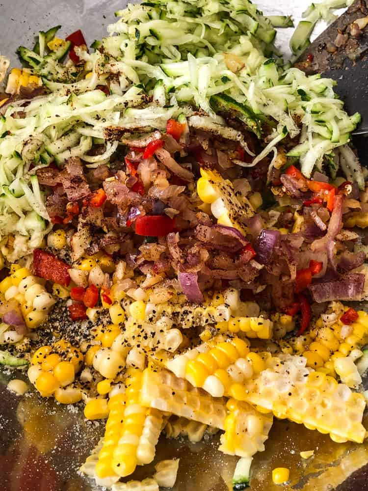 Bowl full of grated zucchini, corn, onions, and red pepper for corn fritters.