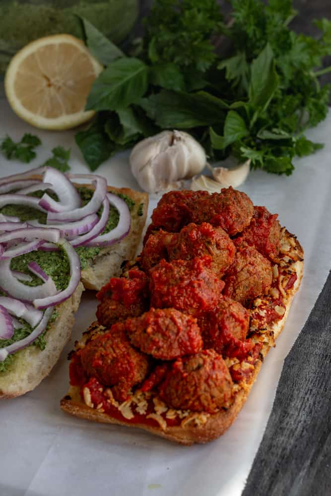 Open face vegan meatball sub sandwich on a cutting board with red sauce and onions.