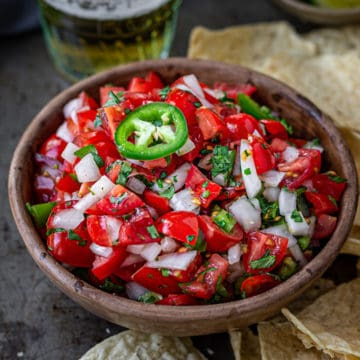 Bowlful of pico de gallo on a tray of taco chips and a glass of beer.