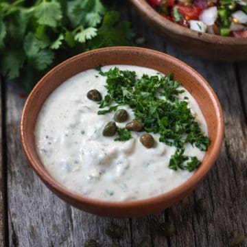 Vegan tartar sauce in bowl topped with capers and chopped parsley.