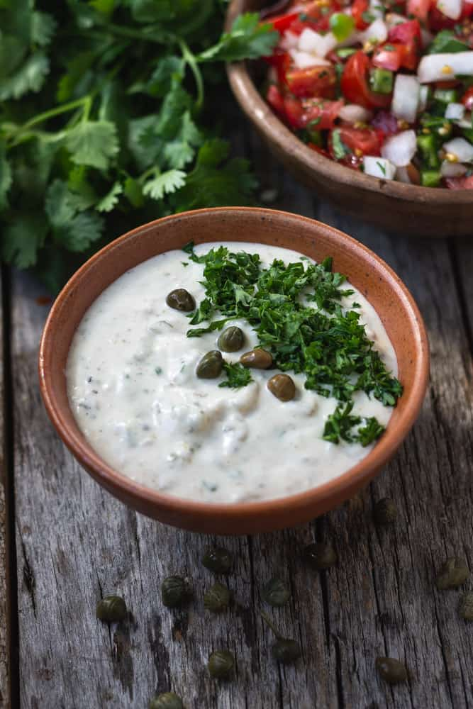 Dish of creamy vegan tartar sauce topped with capers and chopped parsley.