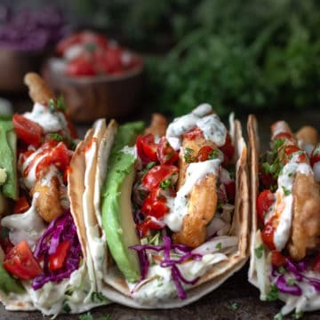 tofu fish tacos with tangy sauce on a tray with salsa and fresh herbs