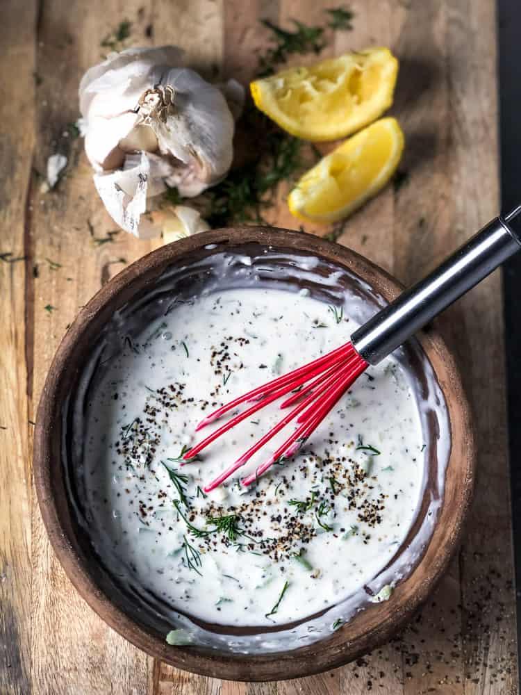 Overhead shot of creamy tzatziki sauce on board with head of garlic and lemon wedges.