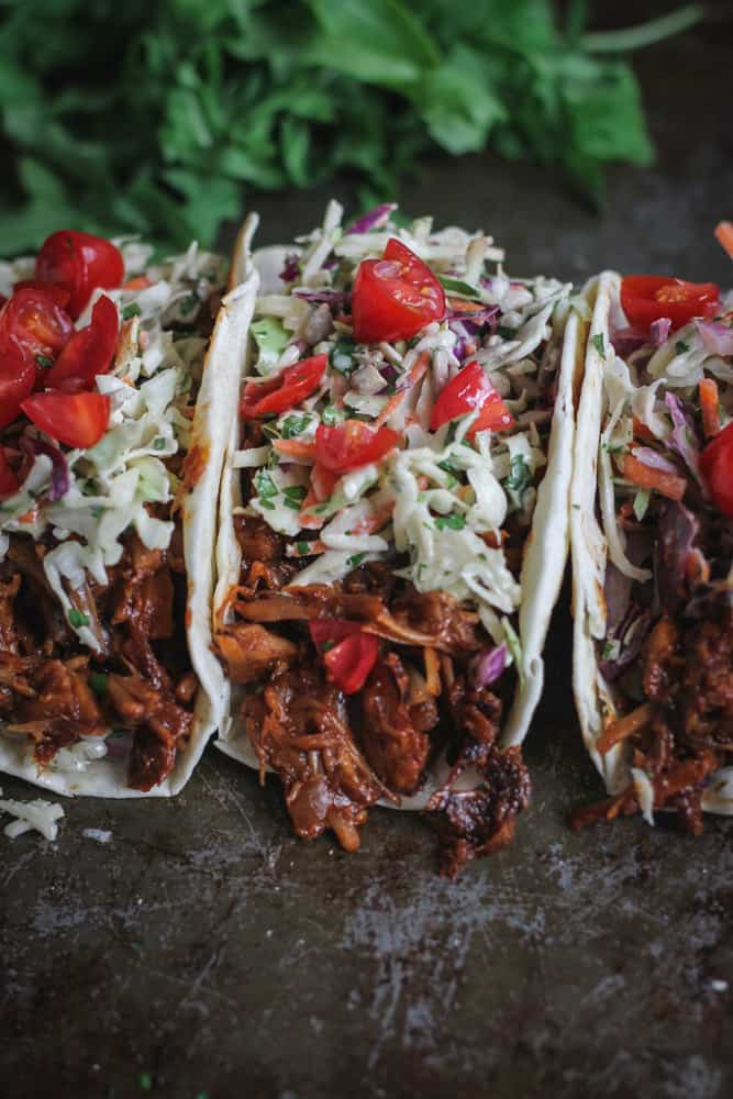 Three taco shells filled with BBQ jackfruit, piled high with creamy slaw and tomato chunks.