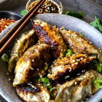 vegan potstickers with maple-soy dipping sauce served in a bowl