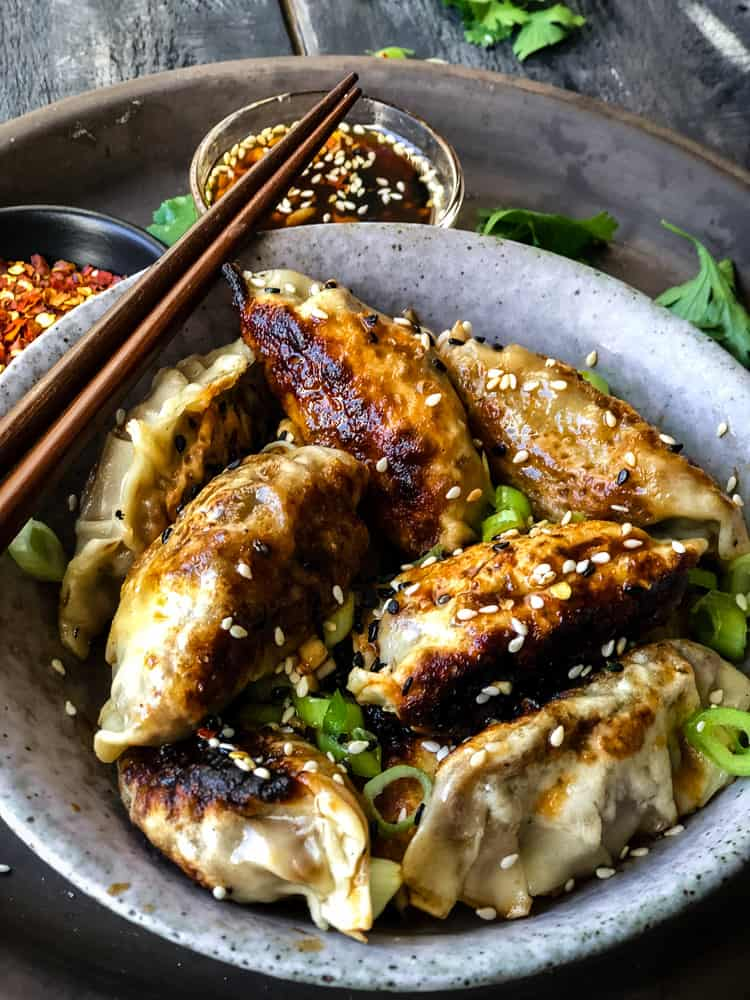 Bowlful of vegan potstickers/dumplings with spicy maple dipping sauce.