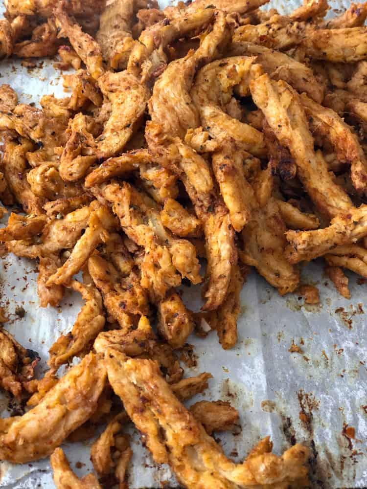 Spicy vegan chicken tenders called soy curls baking on a cookie sheet.
