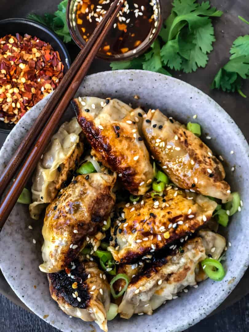Vegan potstickers/dumplings in a bowl with dipping sauce.