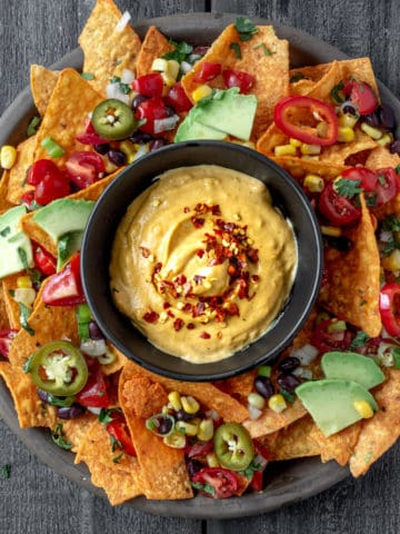 vegan queso cheese sauce on plate of nachos