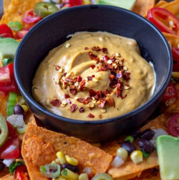 A bowlful of vegan queso cheese sauce on a tray surrounded by taco chips.