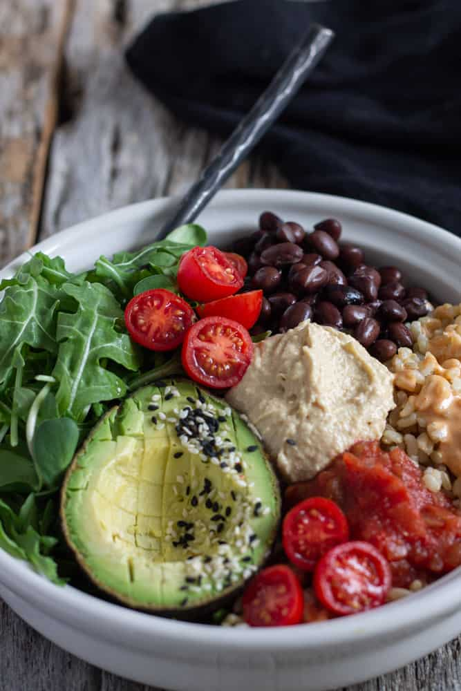 Vegan rice bowl with beans, salsa, avocado and hummus.