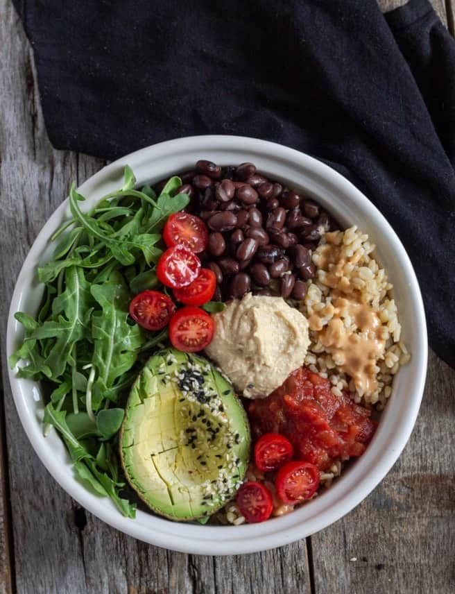 Vegan rice bowl filled with greens, black beans, salsa, avocado half and tomatoes.