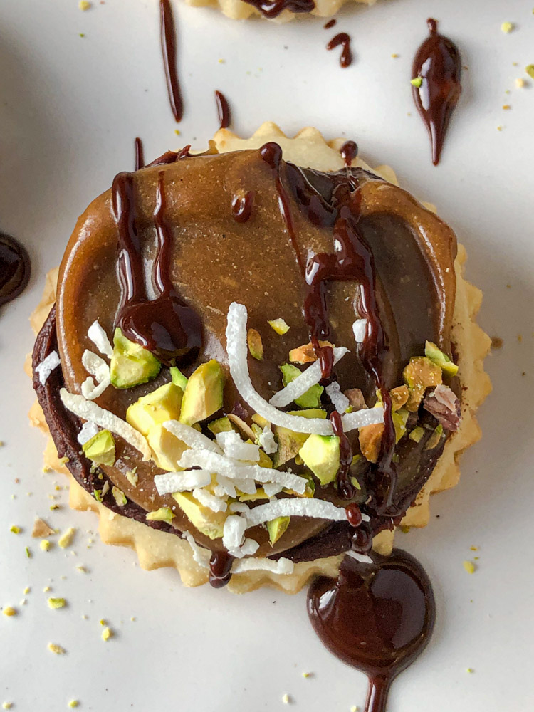 Overhead shot of salted caramel millionaire cookie with crushed pistachios and chocolate drizzle.