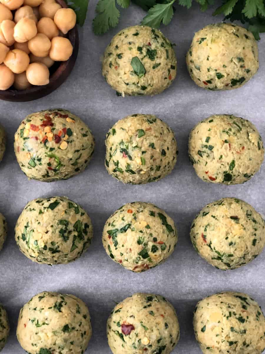 Falafel balls rolled on a baking sheet ready for the oven.