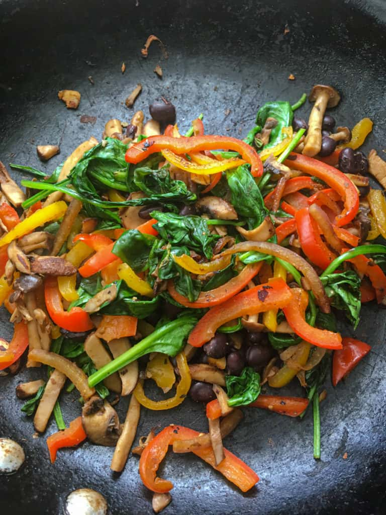 Peppers, spinach, mushrooms frying in a skillet.