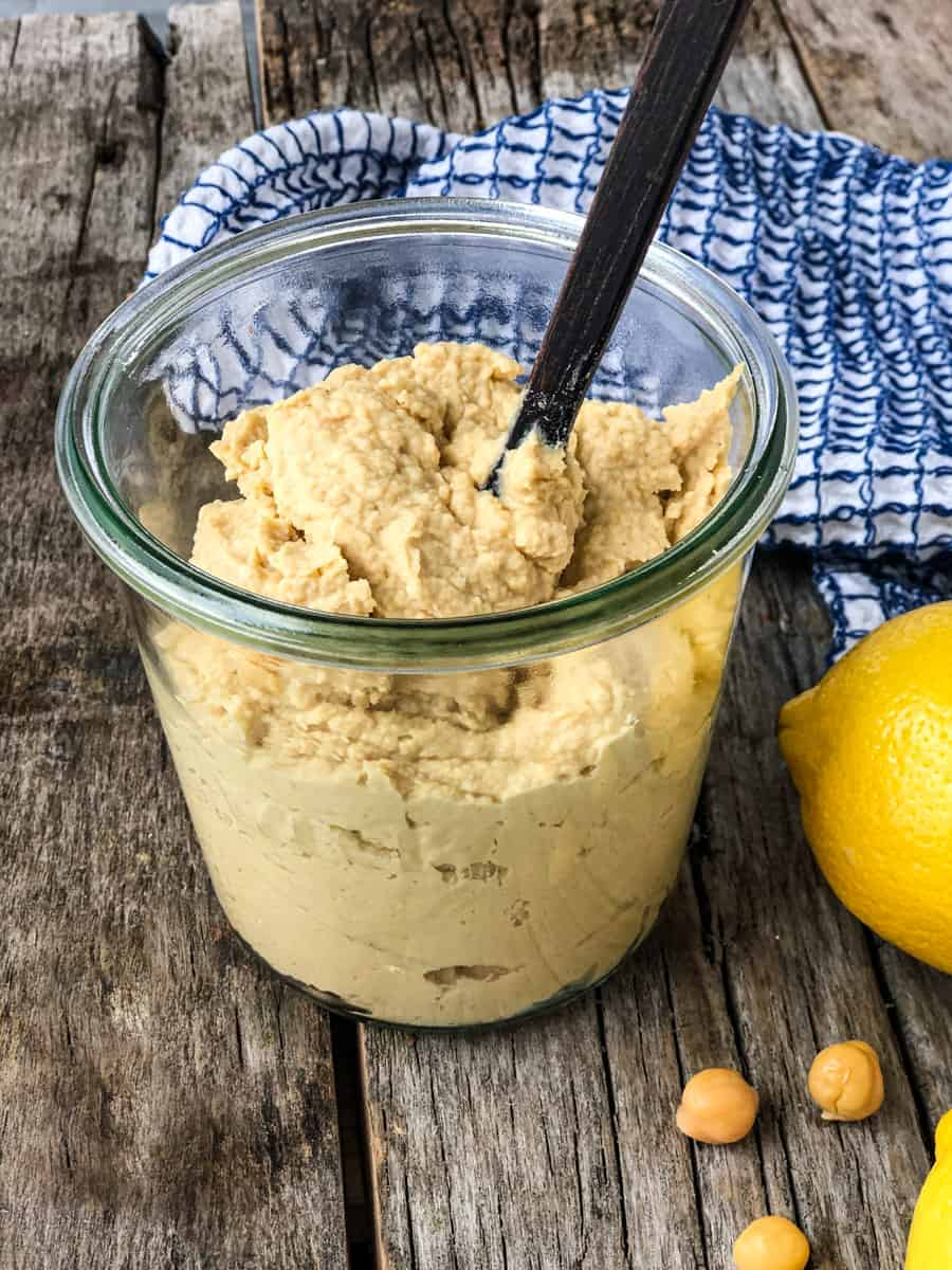 Classic hummus in a jar with a spoon surrounded by chickpeas and lemon on a serving board.