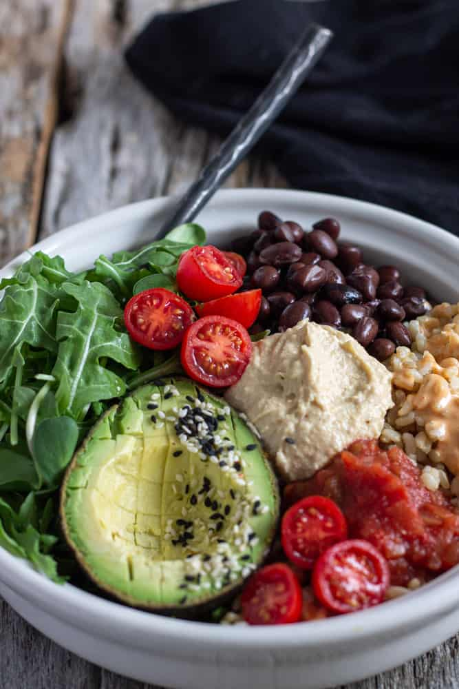 Tomato avocado bean and rice in a bowl with homemade hummus.