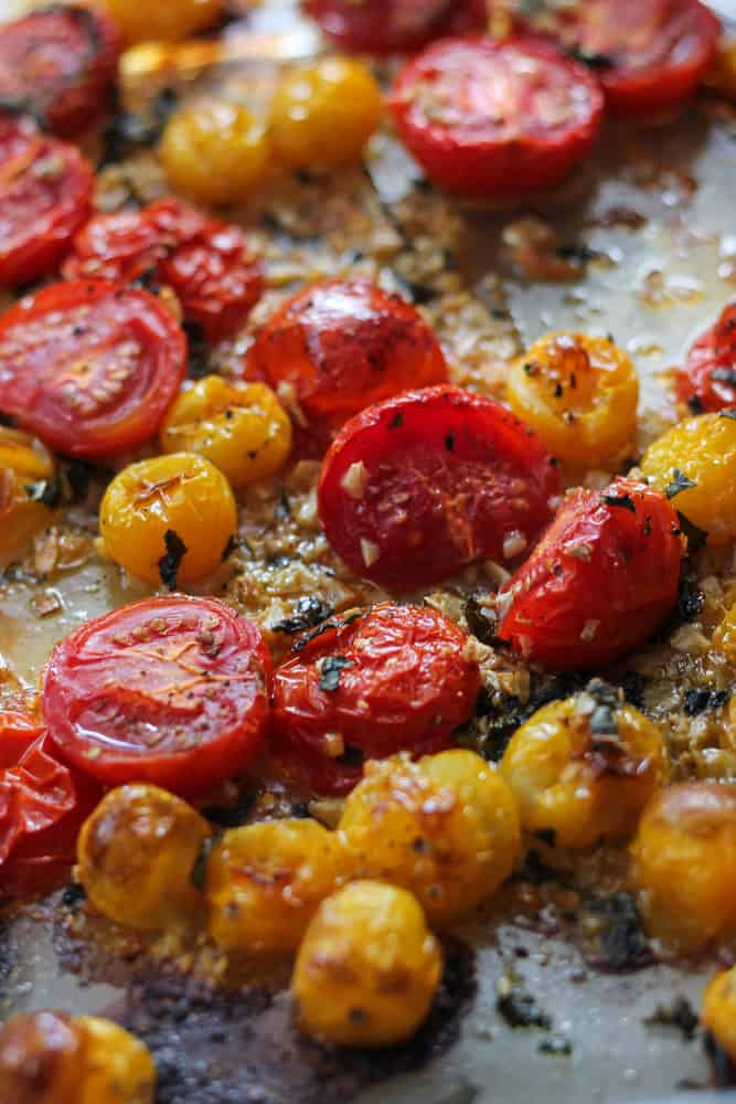 Large bowls of lemon fennel orzo topped with baked tomatoes served on a cutting board.