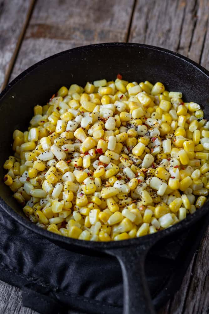 Bowl of grilled corn topped with black pepper and red pepper flakes.
