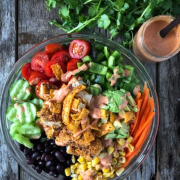 Chopped vegetable salad with vegan chicken and spicy dressing in a bowl.