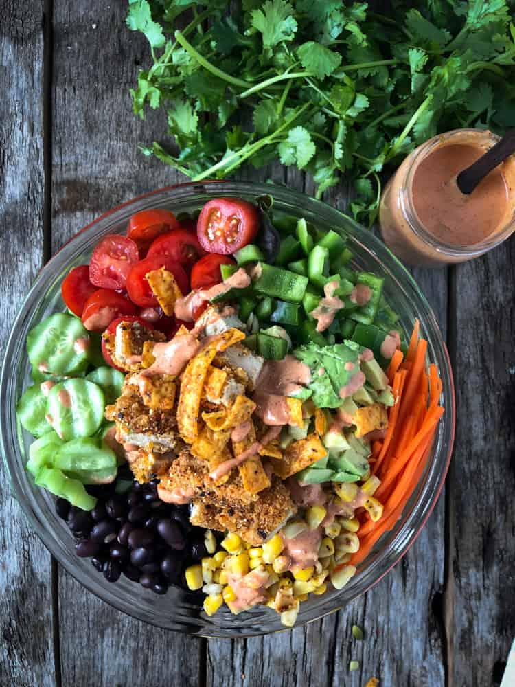 Chopped vegetable salad with vegan chicken and spicy dressing served in a bowl.