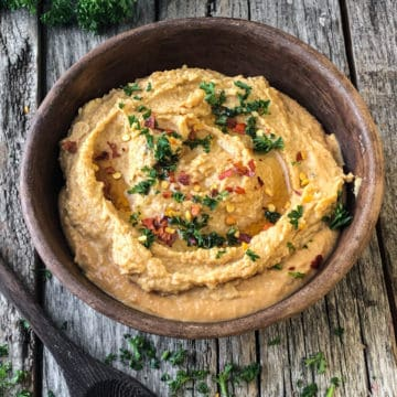 spicy hummus in a bowl with a sprinkle of parsley and hot pepper flakes