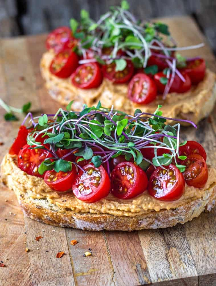 Spicy hummus on sourdough toast with fresh cut tomatoes and sprouts on top.