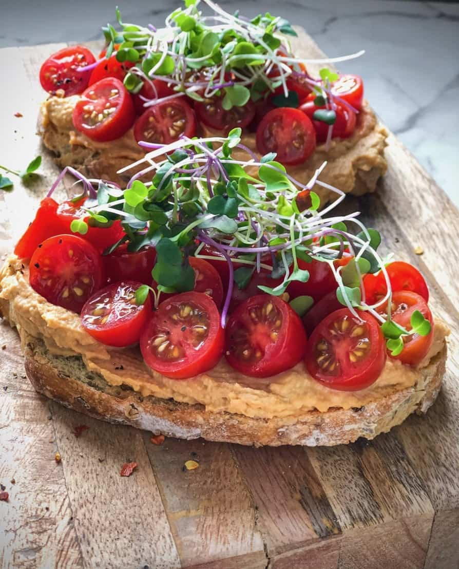 Spicy hummus on sourdough toast topped with halved cherry tomatoes and sprouts.
