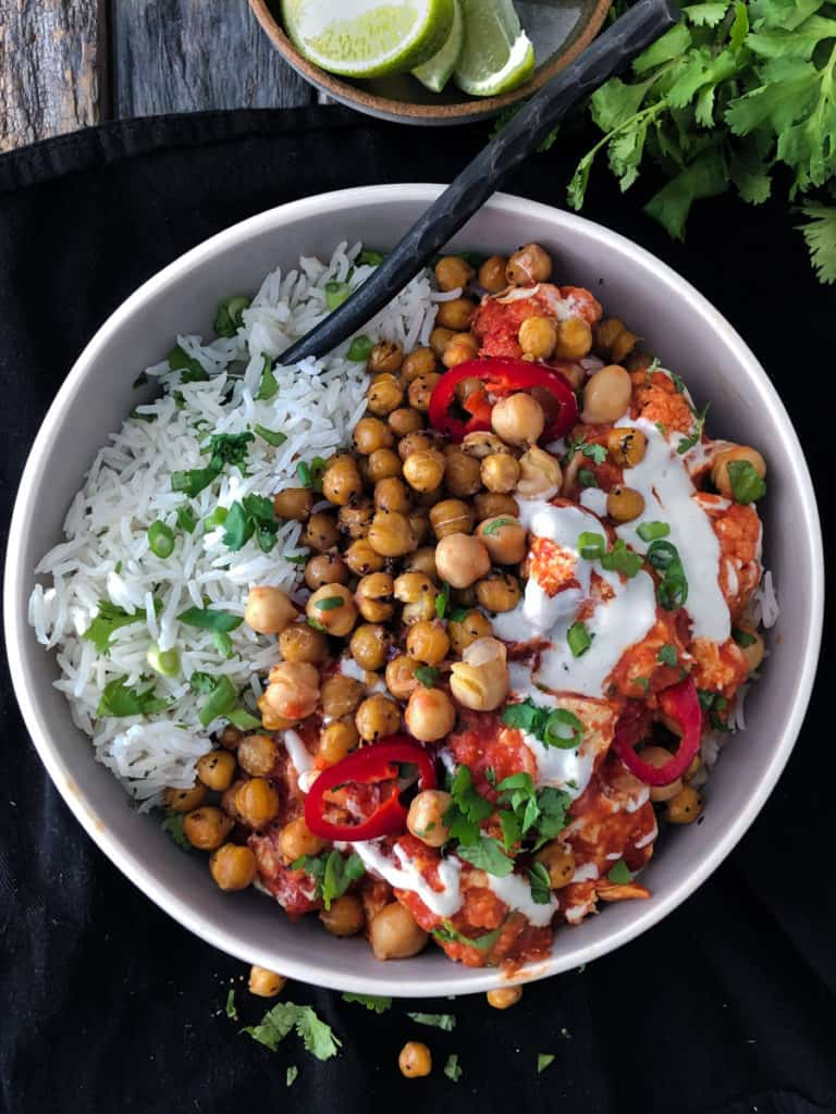 creamy cauliflower, tofu and chickpea curry in a bowl served with rice