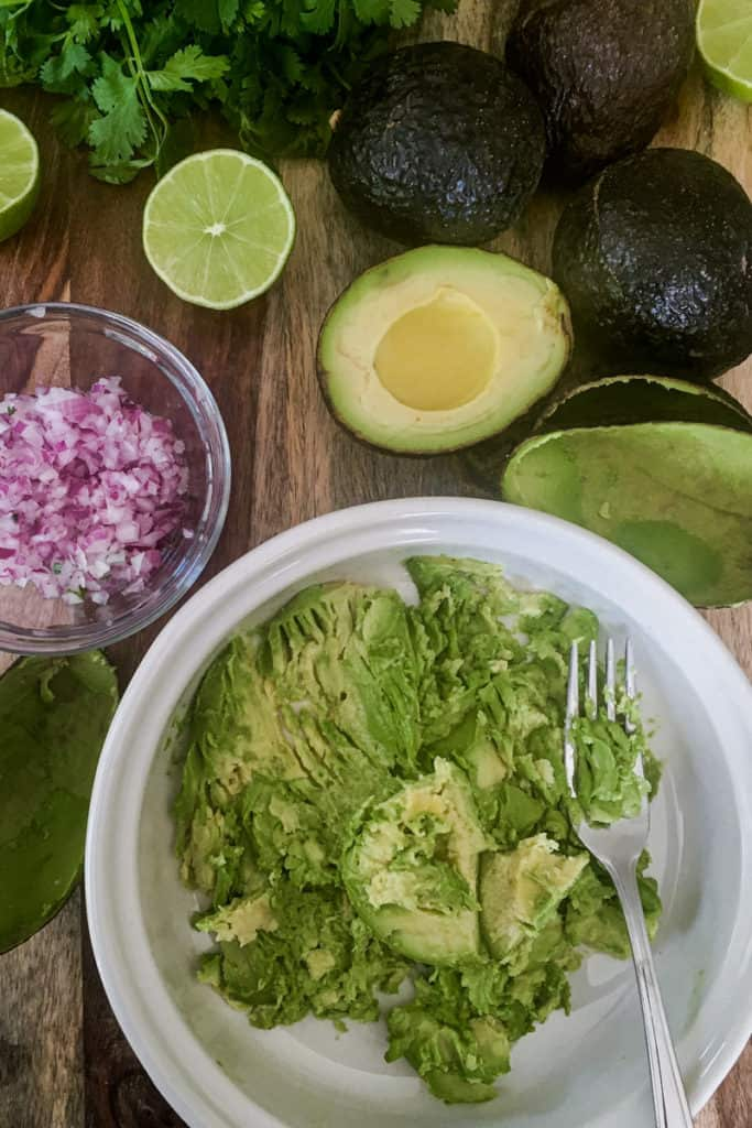 guacamole in a bowl surrounded by limes, cilantro, and avocados