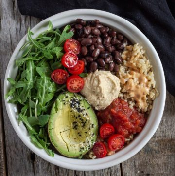 Vegan rice bowl with black beans, rice, hummus, avocado, tomatoes and salsa.
