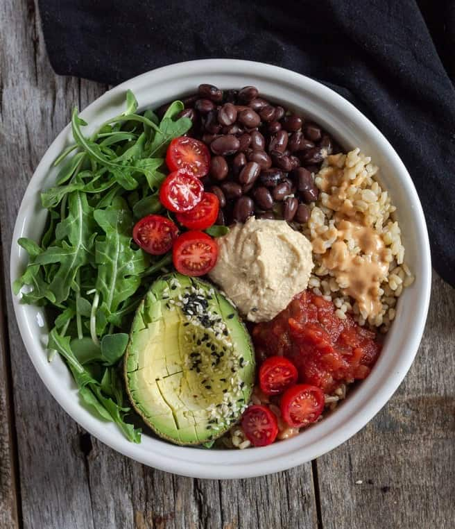 Spicy hummus in a buddha bowl with piles of rice, beans, greens, avocado and salsa.