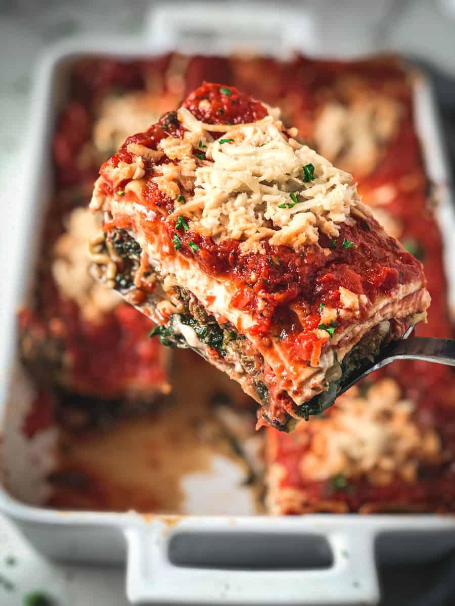 Vegan lasagna slice being lifted out of baking pan.
