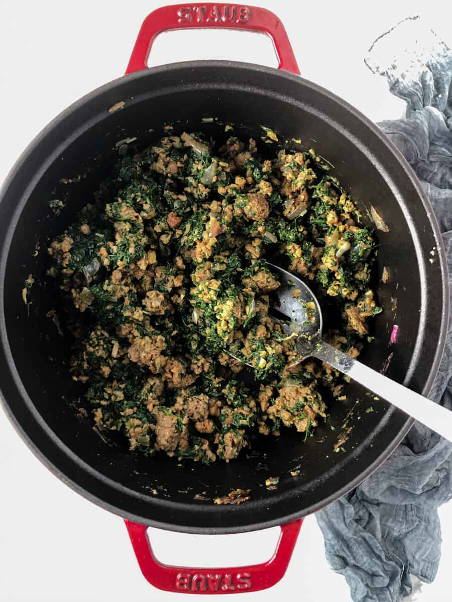 Meaty, spinach and onion mixture frying in a dutch oven.