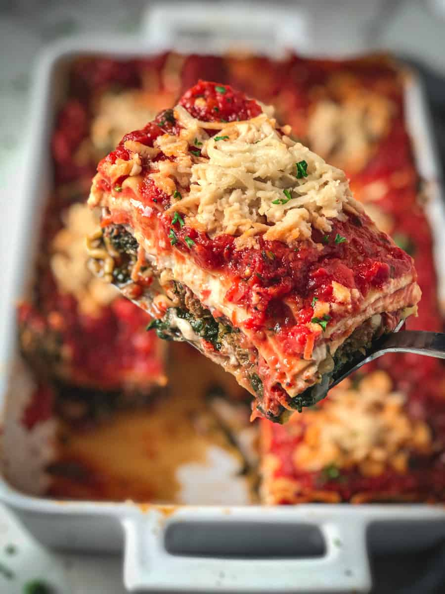 One piece of vegan lasagna being lifted out of a pan of lasagna.