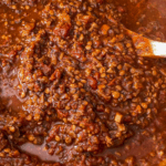 Close up of lentil bolognese sauce simmering in a pot.