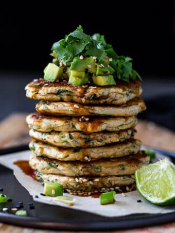 Big Stack of green onion pancakes topped with avocado and onions.