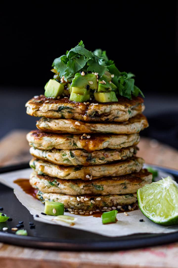 Stack of savory spinach pancakes with avocado and cilantro on top.