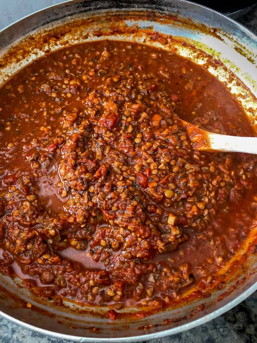 A pan of rich lentil and mushroom bolognese sauce simmering in a pot.