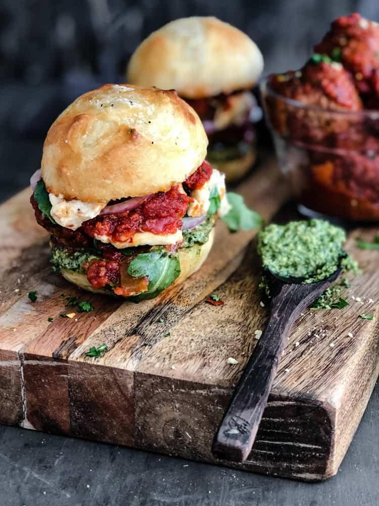 meatball bun in marinara sauce and pesto on a cutting board