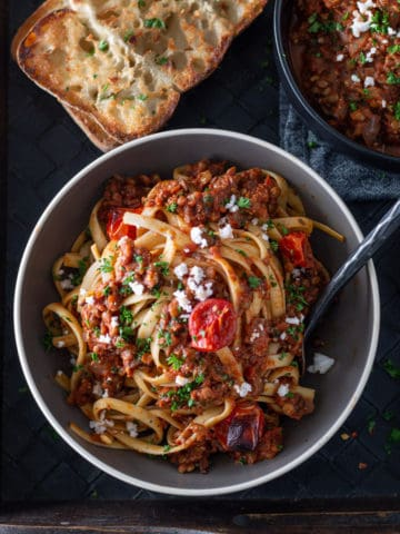 bowl of pasta with lentil bolognese sauce and french bread