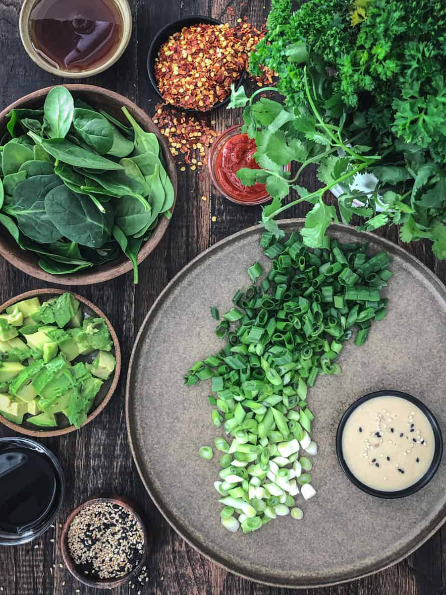 Ingredients for savoury green onion and spinach pancakes on a cutting board.