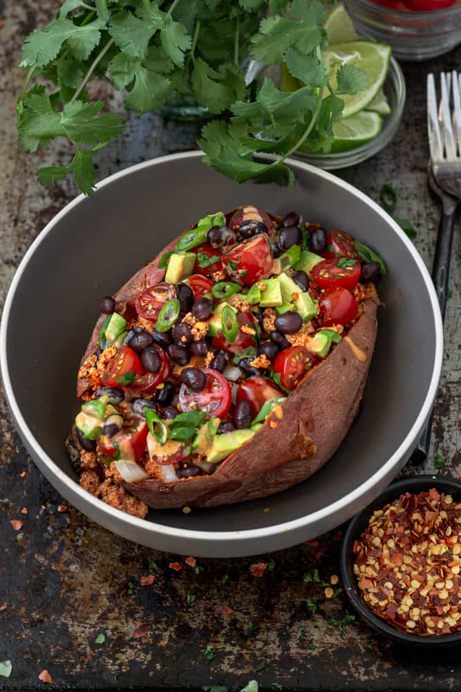 Taco flavoured taco crumbles stuffed in a baked sweet potato topped with avocado, beans, and tomatoes and drizzled with sauce.