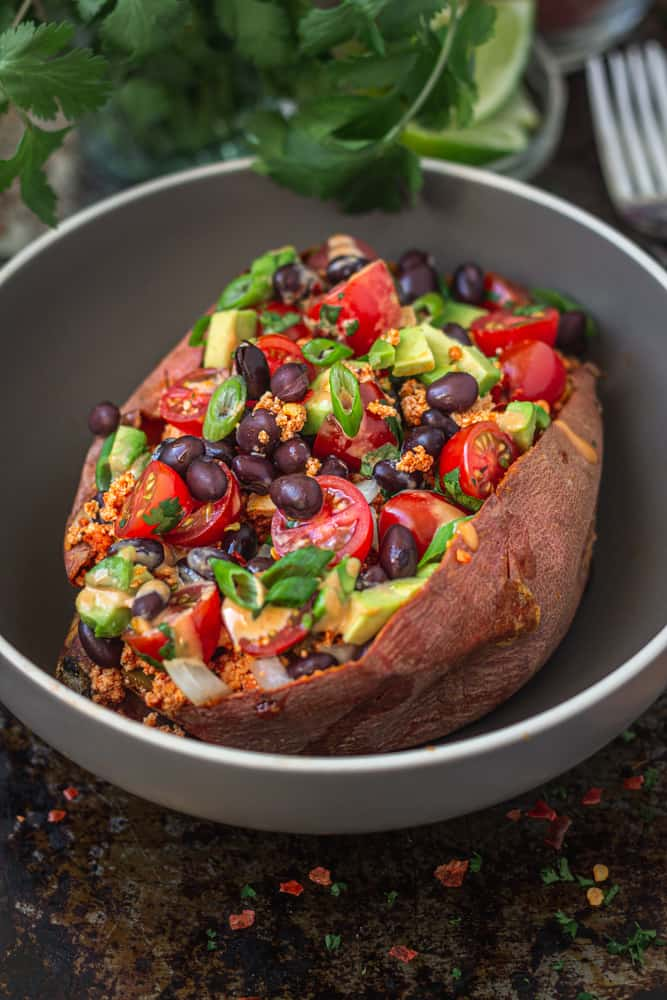 Taco flavoured tofu crumbles stuffed in a baked sweet potato with avocado, beans, and tomatoes, served in a bowl.